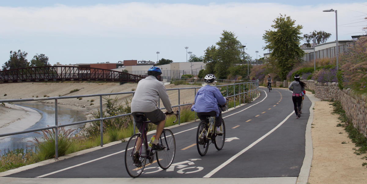 People ride bikes and jog on a separated, multi-use bicycle path.