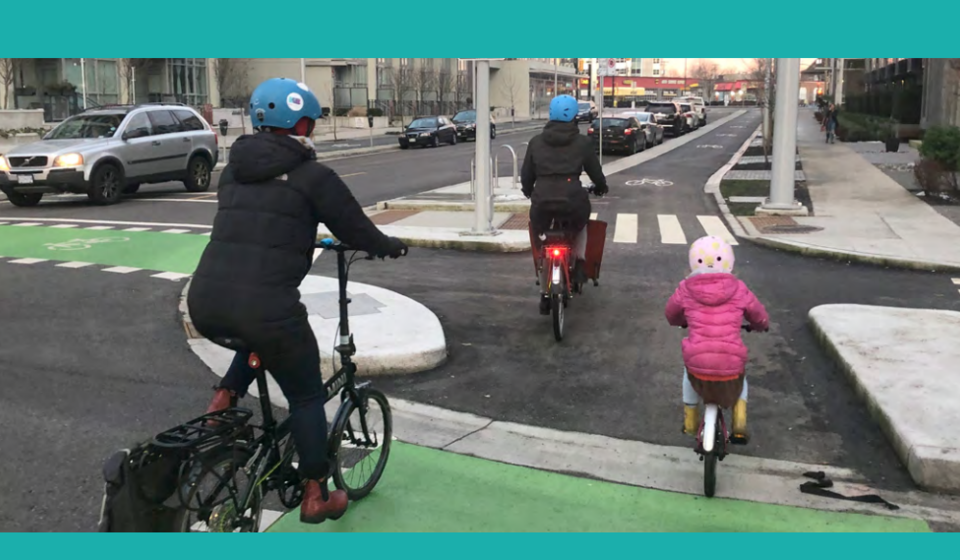 Family bicycling through city intersection