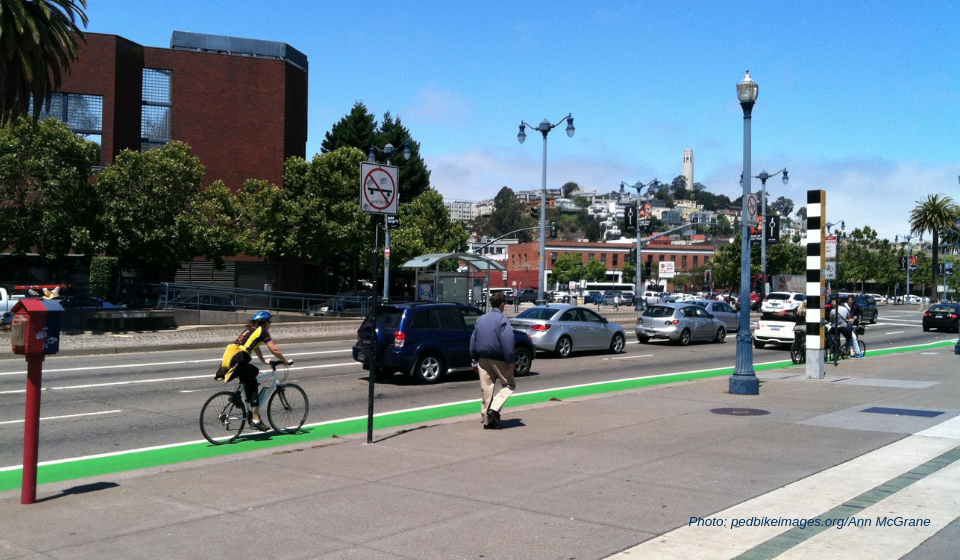 A woman bikes on a green painted bike lane and a man walks on the sidewalk in an busy urban environment.