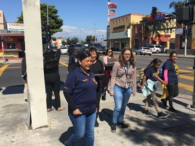 Karla Vilchys walking hand in hand with her child during the South LA CPBST Site Visit